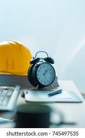 Architecture project deadline, vintage alarm clock on office desk in architectural and interior design studio