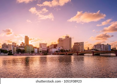 the architecture of Recife in Pernambuco, Brazil showcasing its historic building from the 17th century at sunset by the Capibaribe river.