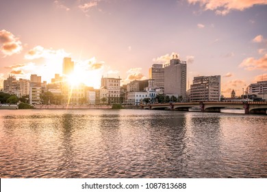 The architecture of Recife in the state of Pernambuco, Brazil at sunset showcasing the Capibaribe river and its historic buildings.