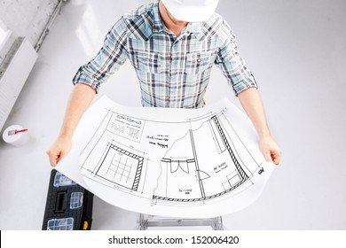 architecture and renovation concept - male architect in helmet with blueprint