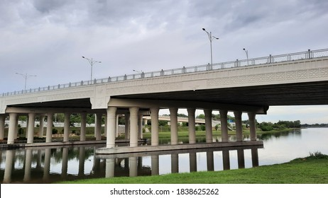 architecture of the simple bridge at the lake of Putrajaya. Reflection image of brigde with clear blue sky.