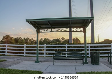 Architecture of a space covered with a dark green bench and a wastebasket in the Celebration district. In the background a beautiful landscape of trees and shrubs in the late afternoon.