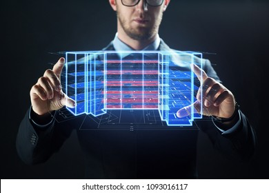 architecture, technology and construction concept - close up of businessman with virtual building blueprint projection