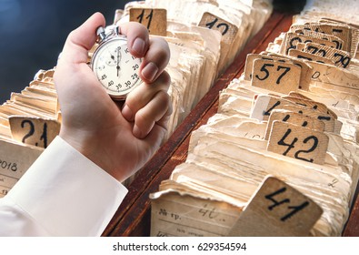 Archive file folders in drawer and stopwatch in male hand
