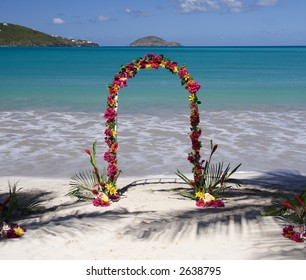 Archway decorated with colorful flowers on a caribbean beach