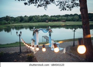 The archway with flowers  for wedding ceremony stands near lake