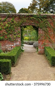 Archway into an english walled garden with Box hedging