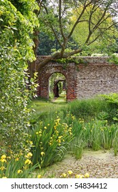 Archway into an English Walled garden with irises around a pond