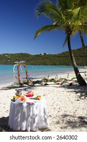Archway and table decorated with flowers and fruits on a caribbean beach