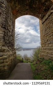 archway under a castle looking out to the sea