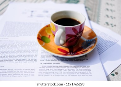 Arco, Italy - September 22, 2018: lively colors on a flowerish designed coffee cup of italian espresso while studying scientific paper.