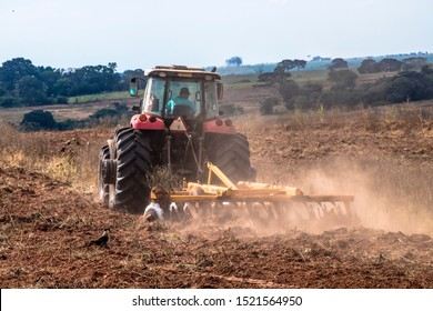Arco-Iris, Sao Paulo, Brazil, May 10, 2019. Farmer plows his tractor from a degraded pasture area and Carcará hawks seek food in the rural area of Arco-Iris, in Sao Paulo State