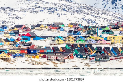 Arctic city panorama with colorful Inuit houses on the rocky hills covered in snow with snow and mountain in the background, Ilulissat, Greenland