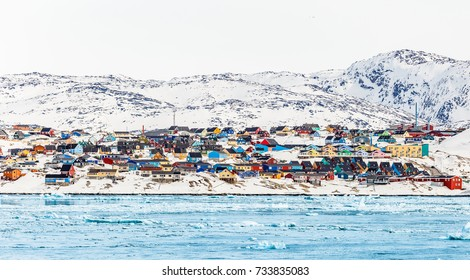 Arctic city panorama with colorful Inuit houses on the rocky hills covered in snow with snow and mountain in the background and blue  icebergs in a foreground, Ilulissat, Greenland