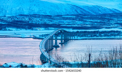 Arctic city of Tromso with bridge - Tromso cantilever road bridge in city - Airplane taking off from the Tromso airport