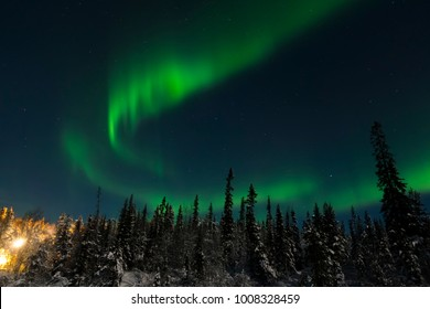 Arctic landscape: aurora borealis at Russian Lapland, Tuloma river near Murmansk. Green northern lights at night star sky.