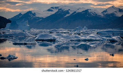 arctic landscape in east Greenland fjords with floating ice blocks glowing at sunset