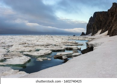 Arctic landscape. The end of June in the far North of Russia. Ice floes off the coast of the Bering Strait and the Arctic Ocean. Cold weather. Cape Uelen, Chukchi Peninsula, Chukotka, Russian Far East
