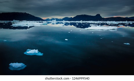 arctic landscape with floating ice blocks glowing at sunset