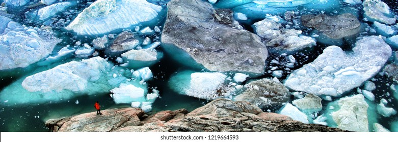 Arctic landscape nature with icebergs tourist manlooking at view of Greenland icefjord - aerial photo. Hikerby ice and iceberg, Ilulissat Icefjord banner panorama.