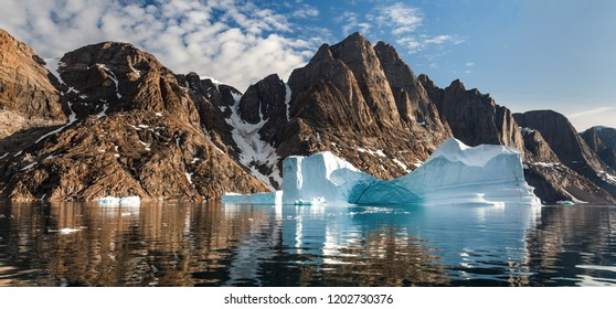 Arctic landscape in summer with high mountains and icebergs floating on the sea in Ofjords, Scoresby Sound, East Greenland