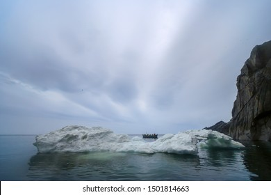 Arctic landscape with a whaleboat among the ice floes in the Bering Strait. The boat of the Chukchi sea hunters. Traditional sea hunting in the Arctic. Cold polar summer. Chukotka, Far East of Russia.