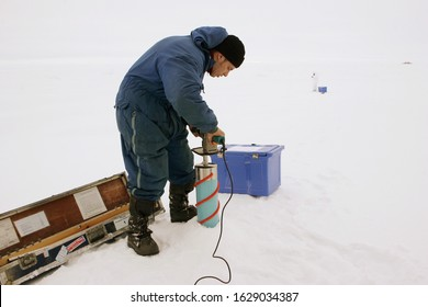 The Arctic Ocean - October 3, 2011: Polar explorer Roman Gouzenko is drilling perennial drift ice to take a sample of Arctic frozen water, another scientist taking samples in the midle ground