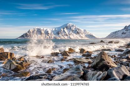 Arctic ocean wave hitting rocks with sunshine mountain at Skagsanden beach, Lofoten island, Norway