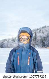 Arctic outdoor winter portrait of a child boy in winter clothing with balaclava against frozen landscape background.