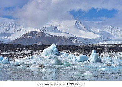 An arctic, polar scene with icebergs floating in Jokulsarlon Lagoon, a glacial lake located in the southern region of Iceland, with snow covered mountains and glaciers in the distance