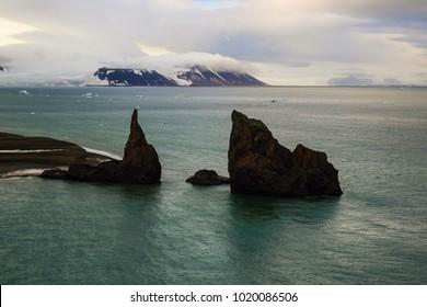 Arctic scene. Columnar rocks, cliffs under cloud sky. North Pole, Arctic ocean.