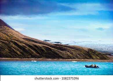 Arctic scenery - mountain slope, melting glacier, pebble beach, bright water of Recherchefjorden and motor boat at the background of blue sky, Spitsbergen island, Svalbard, Norway, Greenland Sea