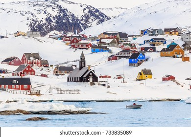 Arctic settlement with colorful Inuit houses on the rocky hills covered in snow with snow and mountain in the background, Ilulissat, Greenland