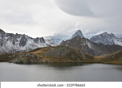 Arctic Vibes at the Swiss Lac de Ferret With the Markedly Triangular Peak of Mont Dolent and other Mountains in the Mont Blanc Range in the Background and Picturesque White and Grey Clouds Above