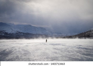 Arctic wind over a frozen river with a cross-county skier in national park Sarek. Lapland, Sweden.