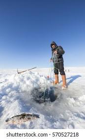 Ardahan, Turkey - January 14, 2017: Fishermen fishing by using fishnet on frozen Cildir lake in Ardahan city of Turkey on January 14, 2017.