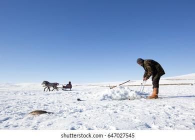 Ardahan, Turkey - January 14, 2017: Fisherman fishing by using fishnet on frozen Cildir lake in Ardahan city of Turkey on January 14, 2017.