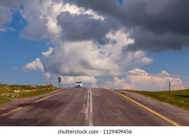 ARDAHAN/TURKEY - JUNE, 27, 2018:The white car is moving in a path that reaches the clouds. Savsat-Ardahan way, Bulbulhan Geçiti.