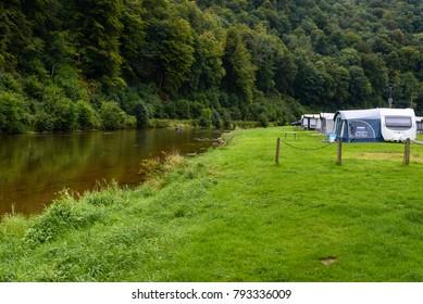Ardennes, Wallonia, Belgium. Caravans or camper trailers set on the river side of river Semois in camp site or camping in Ardennes region of Wallonia in Belgium.
