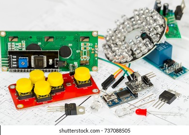 Arduino components and electronic components over electronic diagram, printed wiring, transistors, integrated circuits, capacitors, resistors, LED, semiconductors, infrared leds
