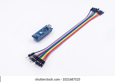 Arduino nano board jumper rainbow cable on isolated white background. Electronic circuit hardware. Soft focus due to shallow DOF.