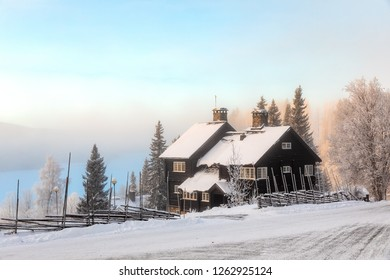 Are, Sweden - Dec 14, 2018: Black wooden house at the Ski Resort Are in Sweden with foggy background down to the valley.
