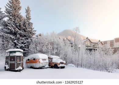 Are, Sweden - Dec 14, 2018: Vehicles covered in snow at the ski resort Are in Sweden with buildings and mountains in background.
