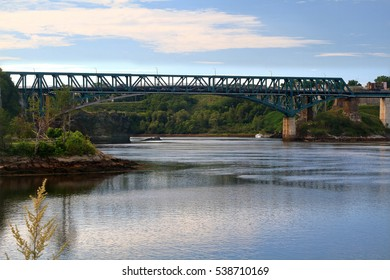 Area and bridge Reversing falls already washed out from tidal erosion on the Saint John River in time of highest tide when the river is flowing in reverse direction with pier and tour cruise ship