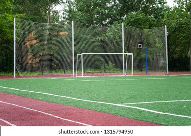 Area of playing field with goal and protective grid for balls catching