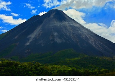Arenal Volcano in Costa Rica with exhalation and ash. Beautiful tropical landscape with active volcano in Central America.