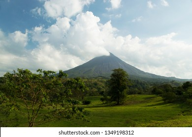 Arenal Volcano in Costa Rica and the lush green valley below. Arenal is surrounded by clouds and fumaroles.