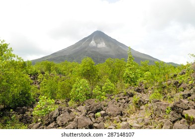 Arenal Volcano in Costa Rica with trees and lava field in the foreground