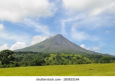 Arenal Volcano on a sunny day in Costa Rica with forest and field in foreground