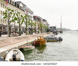 ARENDAL NORWAY - JULY 04, 2019 : Old Building and Tourist boat in Pollen harbour in Arendal, Norway